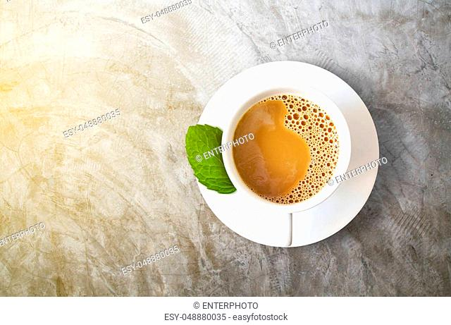 white coffee cup with peppermint leaf isolated on cement background, herbal drink concept