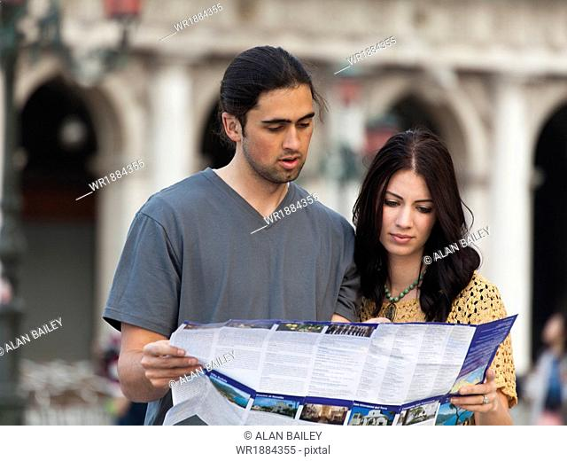 Italy, Venice, Young couple looking at map on St. Mark's Square