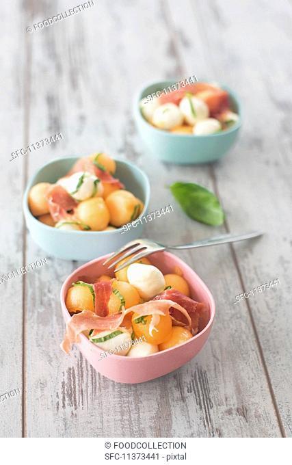 Three bowls of melon salad with mozzarella balls and Parma ham