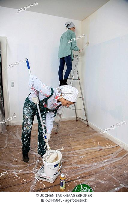 Mother and daughter renovating a room, painting the walls with paint rollers