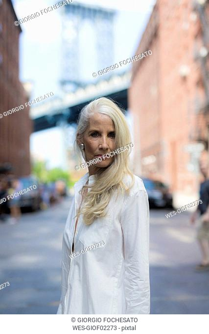 USA, Brooklyn, Dumbo, portrait of serious mature woman wearing white shirt blouse