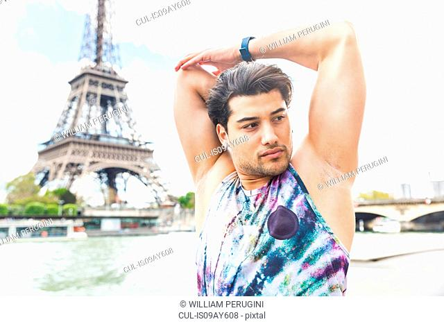 Young man exercising outdoors, stretching, Eiffel Tower in background