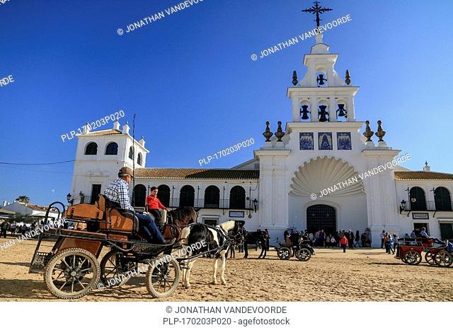 Horse-drawn carriage and pilgrims in front of the white Hermitage of El Rocío / Ermita del Rocío, Almonte, Province of Huelva, Andalucia, Spain