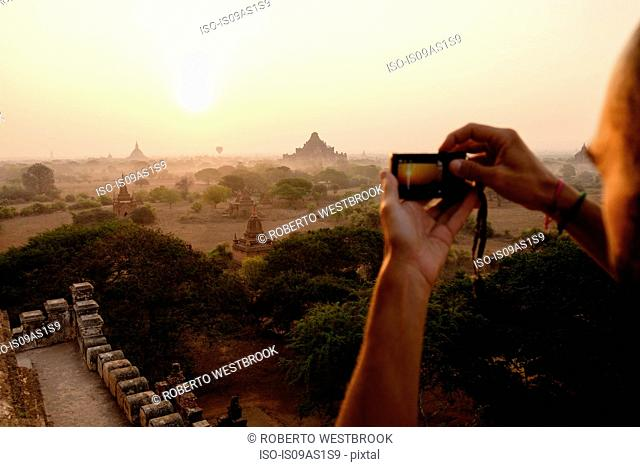 Man taking photograph of view, Bagan Archaeological Zone, Buddhist temples, Mandalay, Myanmar