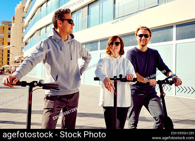 Three best friends young 20s -30s girl and guys spend time outdoors gathered together driving on electric scooter modern land vehicle, easy comfort usage