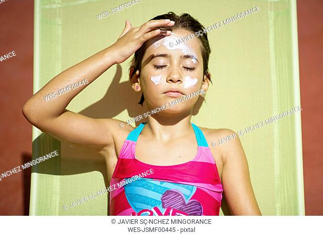 Young girl using suncream