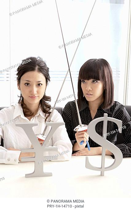 Young women with holding sword and with yen sign and dollar sign in foreground