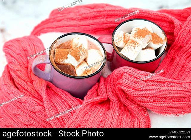 Hot chocolate with marshmallow in pink and violet two cups wrapped in a cozy winter pink scarf on the snow-covered table in the garden