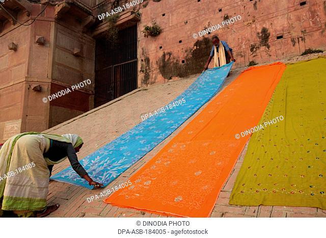 woman drying saris on Ganga River ghat at Varanasi Uttar Pradesh India