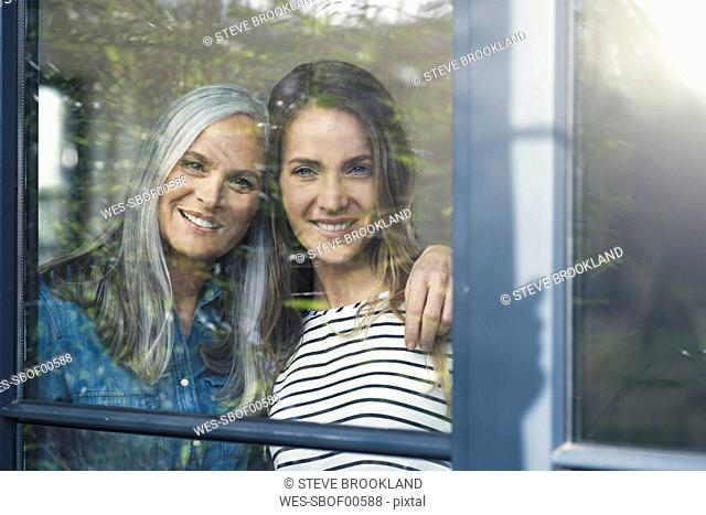 Mother and daughter looking out of window