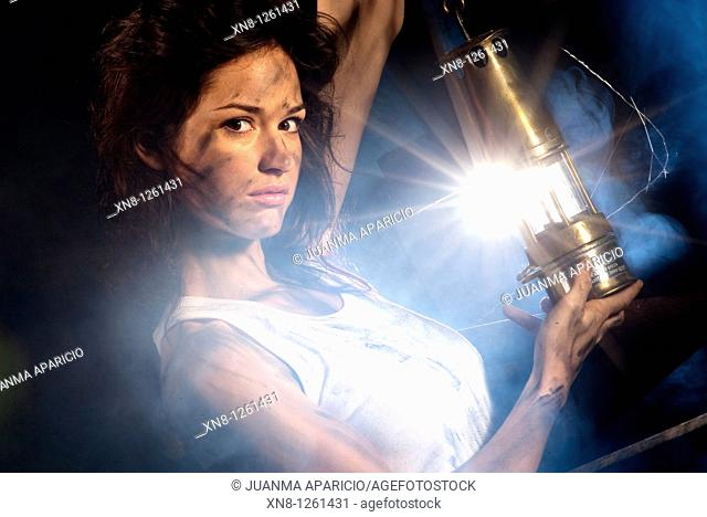 Portrait of young woman wiht miner's lamp representing the work inside a mine