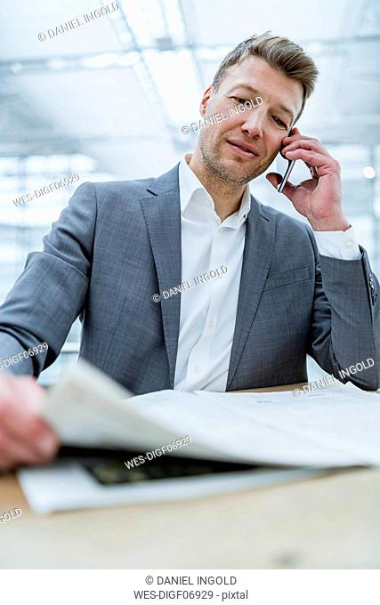 Businessman with newspaper on cell phone in a cafe