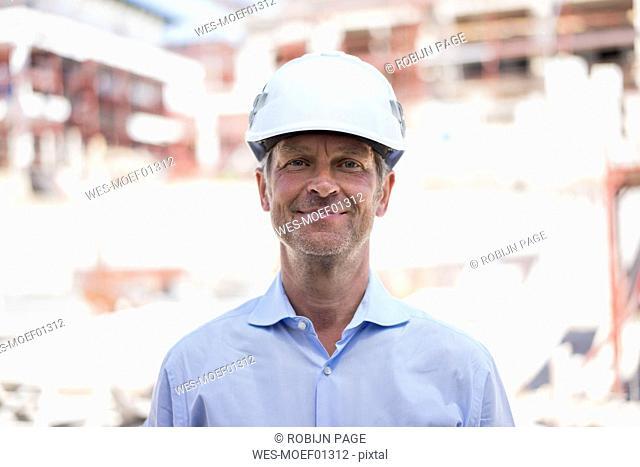 Portrait of confident man wearing hard hat on construction site