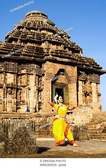 Odissi dancer strikes pose of re-enacts Indian myths such as Ramayana against backdrop of world heritage Sun temple complex in Konarak , Orissa , India MR400