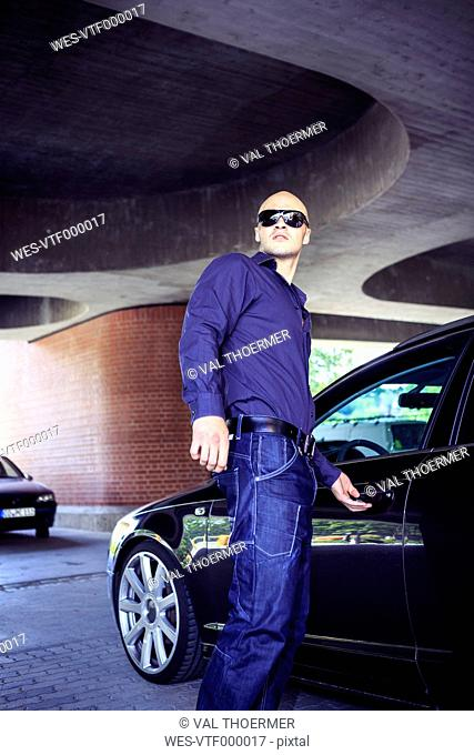 Man with sunglasses next to car under a bridge