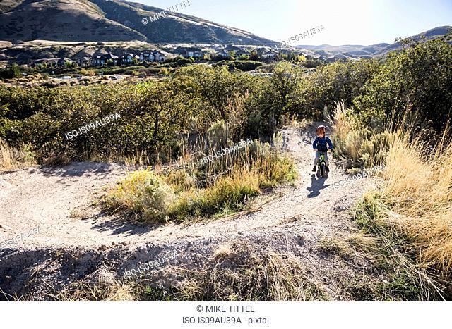 Boy riding balance bike on dirt track, Draper cycle park, Missoula, Montana, USA