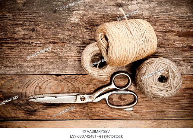 Old rusty scissors and skein jute on wooden table. Top view