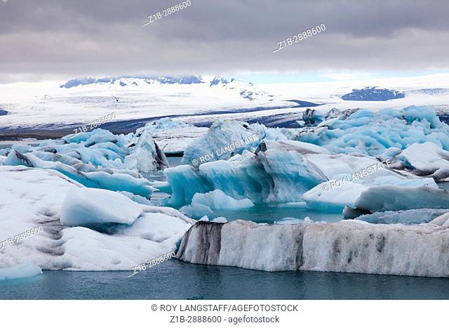 Icebergs floating in the Jokulsarlon glacial lagoon in Iceland under an overcast sky