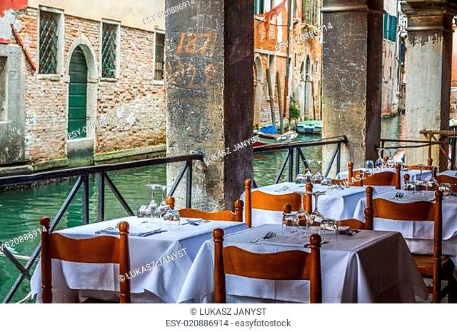 Wooden tables on narrow street among typical colorful houses and small bridge in Venice, Italy