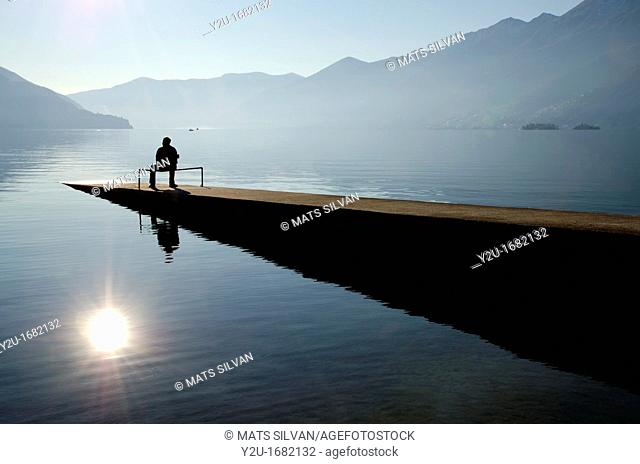 Man sitting on the pier close to the lake with mountains and islands