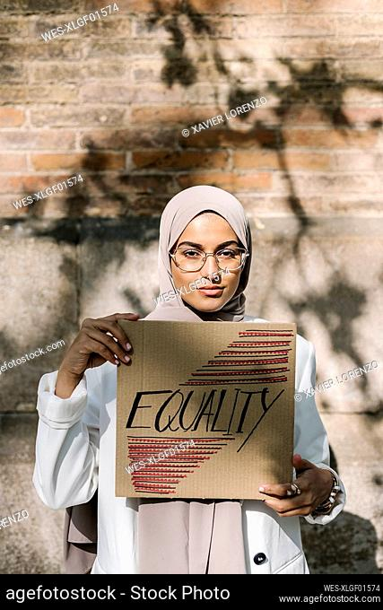 Beautiful woman holding placard with equality text in front of wall