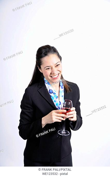 A young business woman holding a glass of wine She is of filipino ethnicity