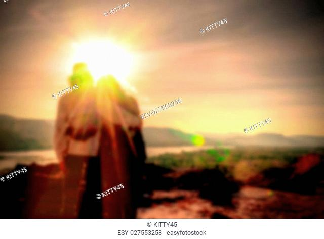 Abstract Blurred and soft photo of the lover standing on the hilltop during sunrise