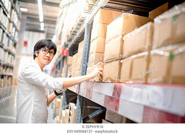 Young Asian man choosing product in paper box package for home decoration. shopping warehousing concept