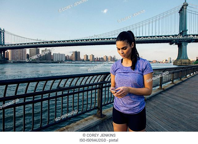 Young female runner reading smartphone in front of Manhattan bridge, New York, USA