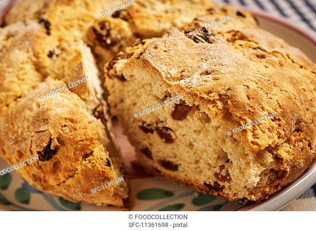 Loaf of Irish Soda Bread with Slice Removed; Slice in Background on a Plate; Butter