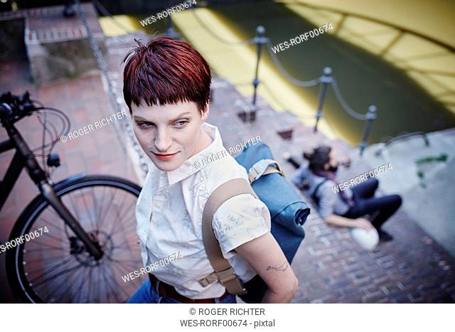 Germany, Hamburg, portrait of woman with dyed hair and backpack