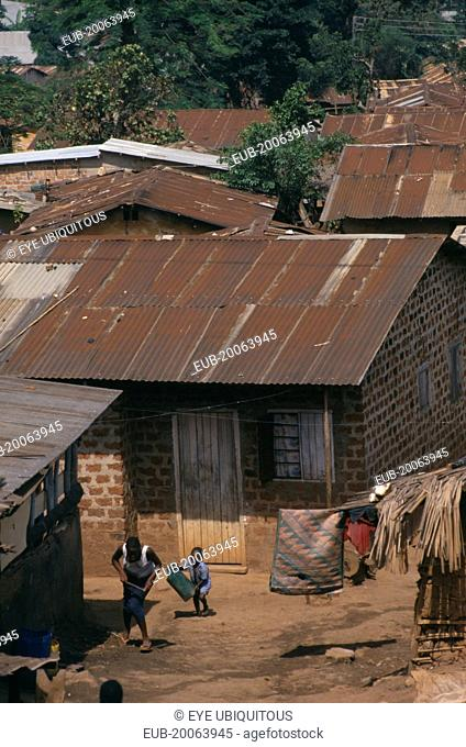 Kamwoyke slum area. Woman and child outside brick hut with corrugated iron roof