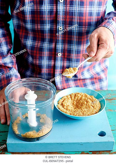 Man preparing fresh mustard recipe step 1, mustard seeds in food processor