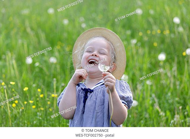 Germany, Bavaria, Girl with dandelion seed, smiling