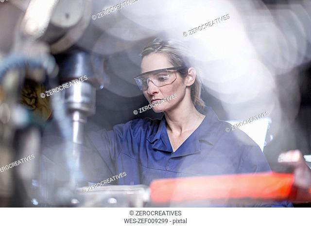Female mechanic wearing safety goggles using drilling machine in workshop