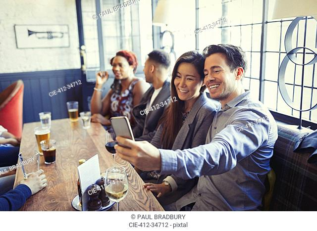 Smiling couple taking selfie with camera phone at table in bar