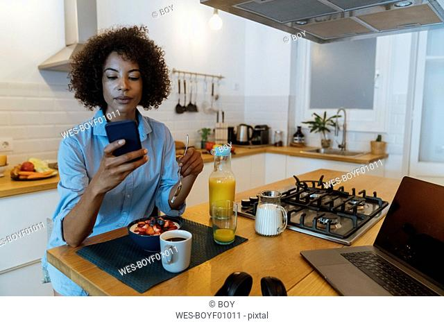 Woman having breakfast in her kitchen, using smartphone