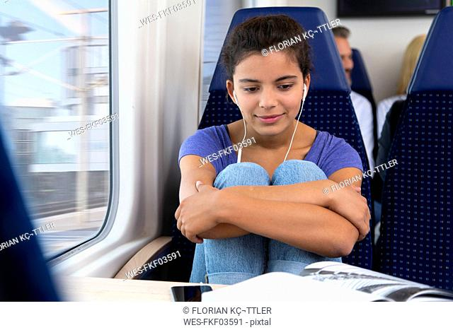 Teenage girl traveling alone by train, listening music, reading a book