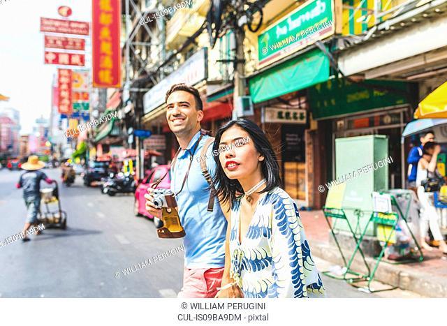 Young tourist couple crossing street, Bangkok, Thailand