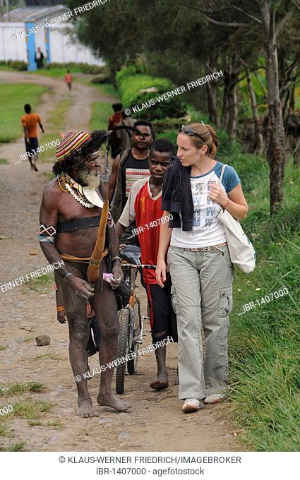 European talking with a Dani, Wamena, Irian Jaya or West Papua, New Guinea, Indonesia, Southeast Asia