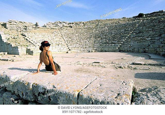 Segesta, Sicily, Italy  Young woman sitting on stage of the ancient Greek theatre at Segesta  Tiered seats of auditorium behind