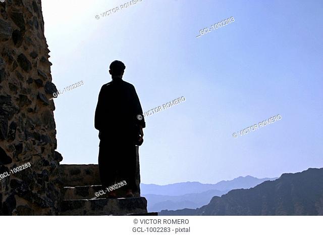 Man looking at Fujeirah mountains, United Arab Emirates
