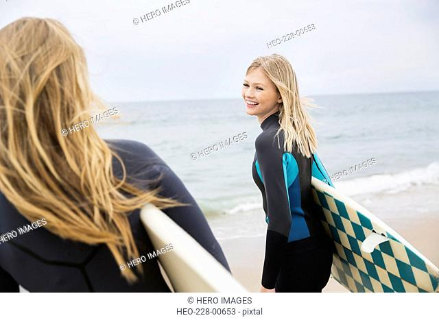 Blonde female surfers with surfboards on beach