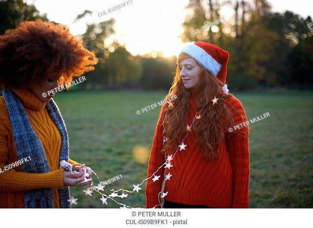 Two young women, in rural setting, young woman wrapped in fairy lights
