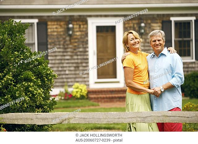 Portrait of a mature couple standing with their arms around each other in front of a house