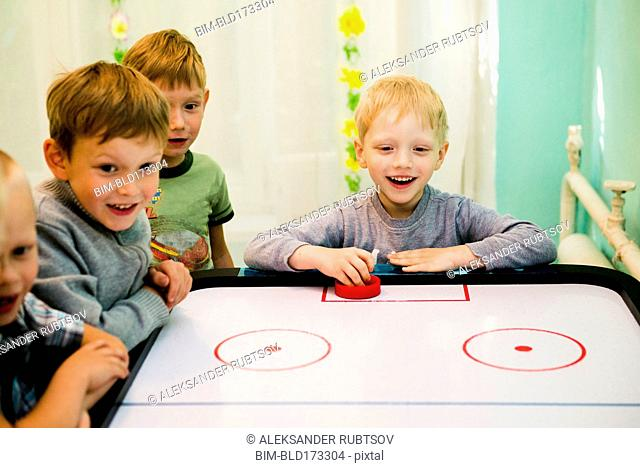 Caucasian boys playing air hockey