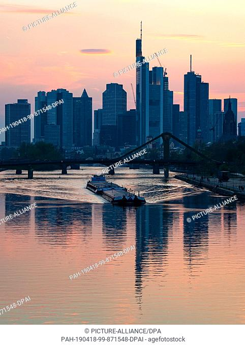 17 April 2019, Hessen, Frankfurt/Main: A ship crosses the Main river shortly after sunset. The skyline is one of the most frequently photographed motifs in...