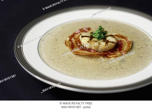 Bowl of Truffle Forest Mushroom Soup with grilled pancetta and scallop garnish
