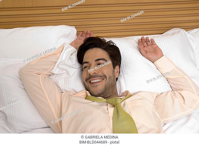 Hispanic businessman laying in bed