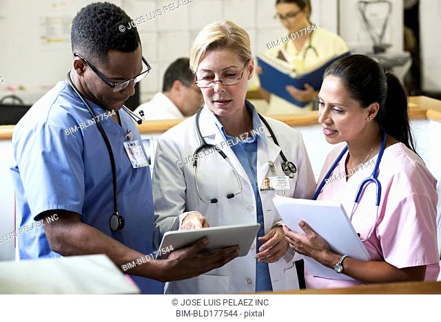 Doctor and nurses using digital tablet in hospital